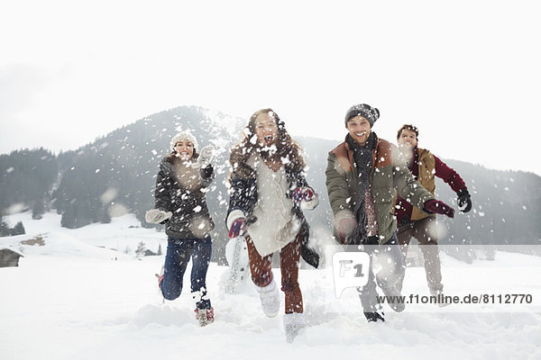 Happy friends playing in snowy field