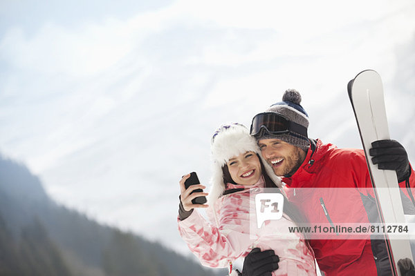 Happy couple with skis taking self-portrait with camera phone