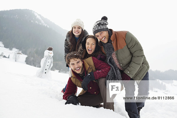 Portrait of happy friends in snowy field with snowman