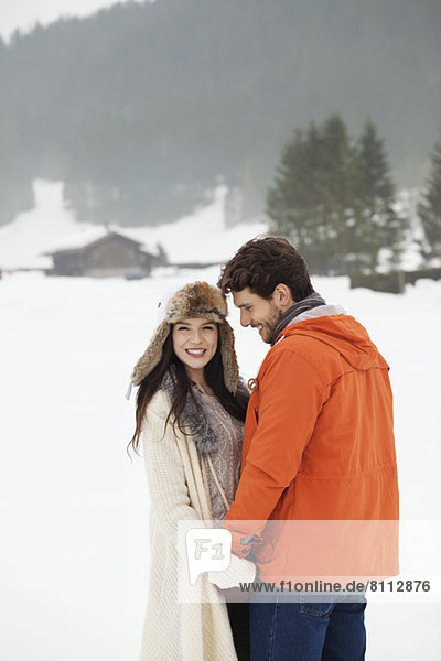 Happy couple holding hands in snowy field