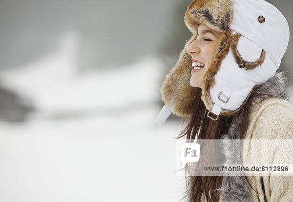 Glückliche Frau mit Fellmütze im Schnee