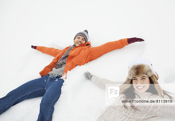 Portrait of happy couple making snow angels