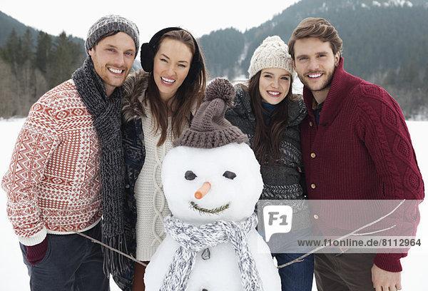 Portrait of happy friends with snowman