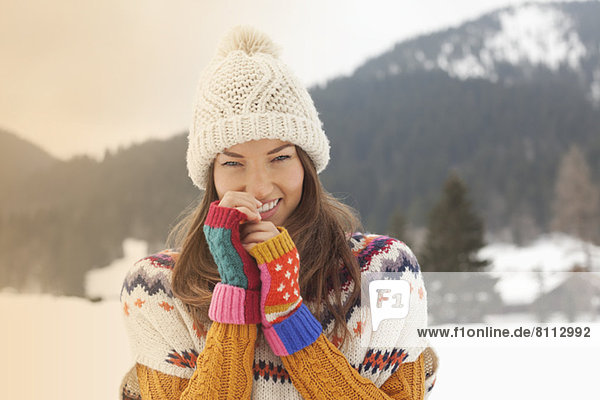Portrait of smiling woman wearing knit hat in snowy field
