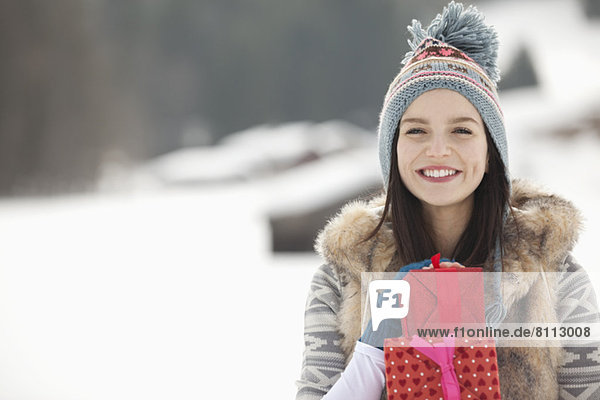Portrait of smiling woman with Christmas gifts in snowy field