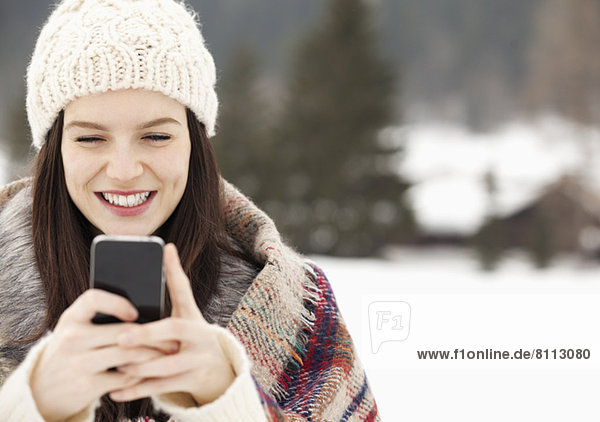 Close up of woman in knit hat text messaging with cell phone