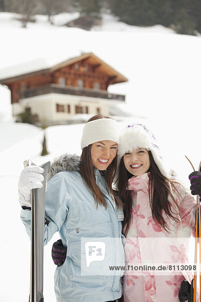 Portrait of smiling women hugging with skis outside cabin
