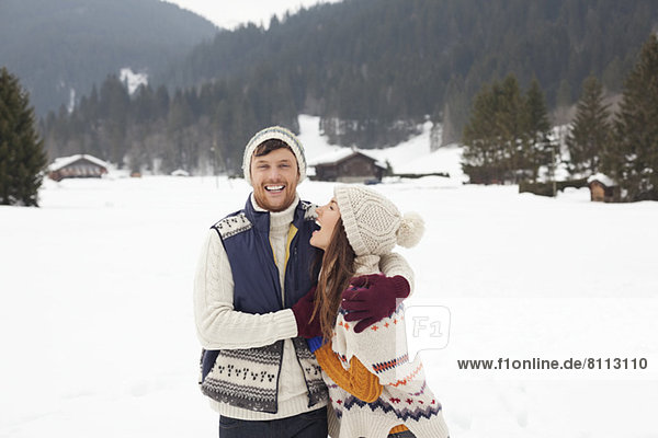 Couple hugging and laughing in snowy field