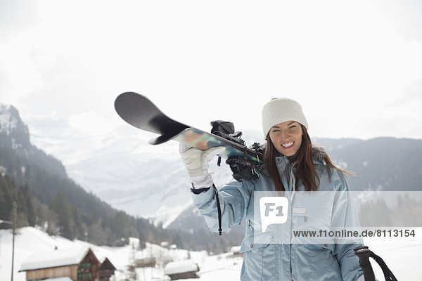 Portrait of enthusiastic woman carrying skis in snowy field