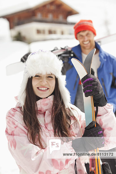 Portrait of smiling couple with skis outside cabin