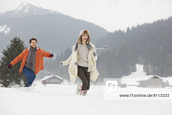 Happy couple running in snowy field