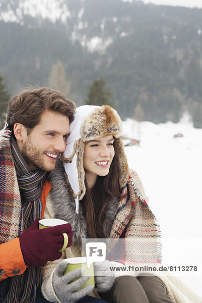Happy couple drinking coffee in snowy field