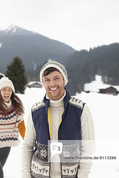 Portrait of happy couple in snowy field
