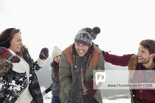 Playful friends enjoying snowball fight
