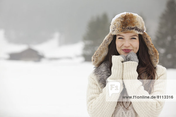 Portrait of smiling woman wearing fur hat and gloves in snowy field