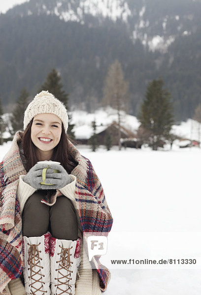 Portrait of smiling woman drinking coffee in snowy field