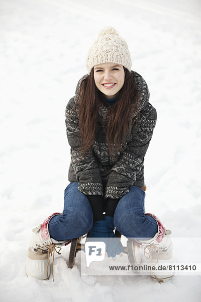 Portrait of smiling woman sitting on sled in snow