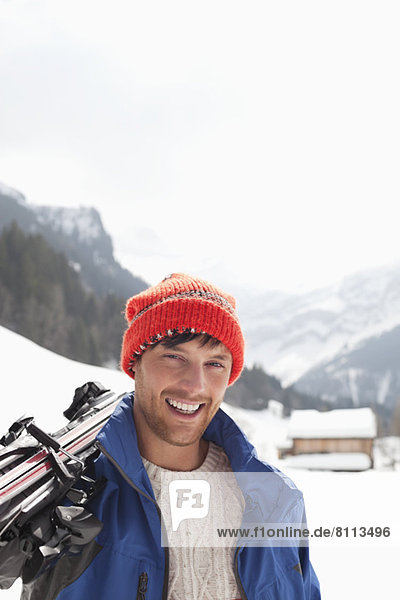 Close up portrait of smiling man carrying skis in snowy field