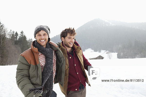 Portrait of happy men walking in snowy field