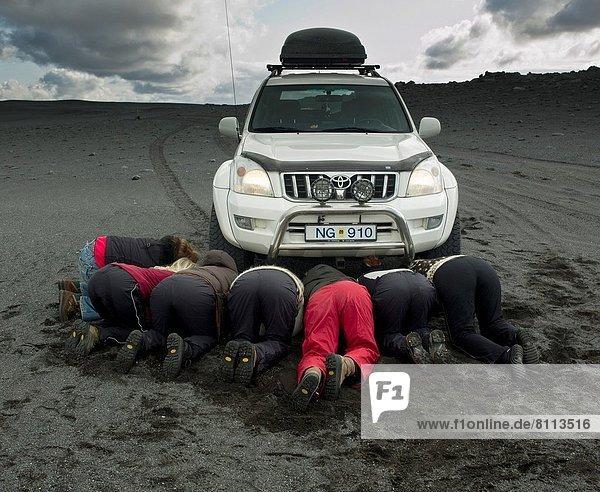Frau  schwarz  Sand  graben  gräbt  grabend  Island