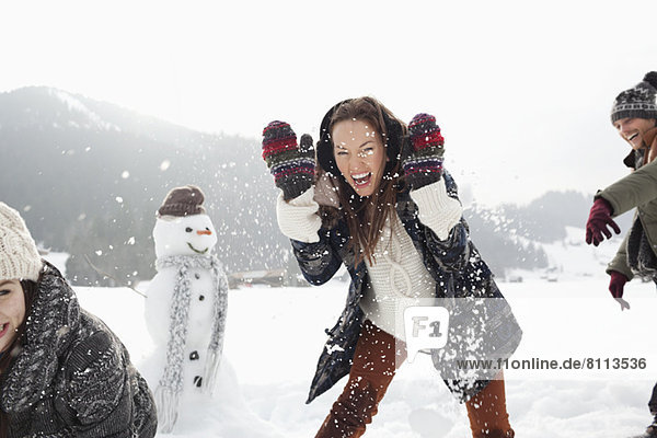 Enthusiastic friends enjoying snowball fight in field