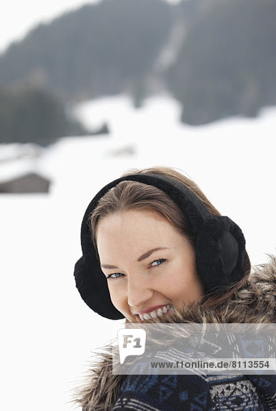 Close up portrait of woman wearing earmuffs in snowy field