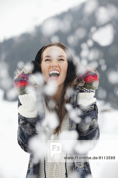 Enthusiastic woman enjoying falling snow