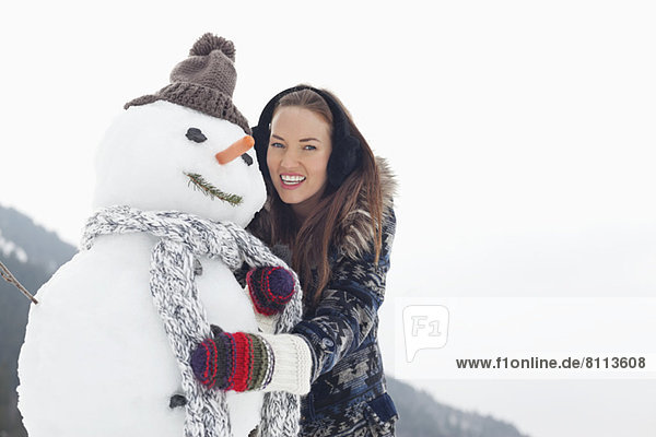 Portrait of happy woman hugging snowman