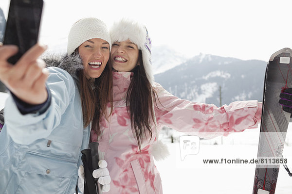 Enthusiastic women with skis taking self-portrait with camera phone in field