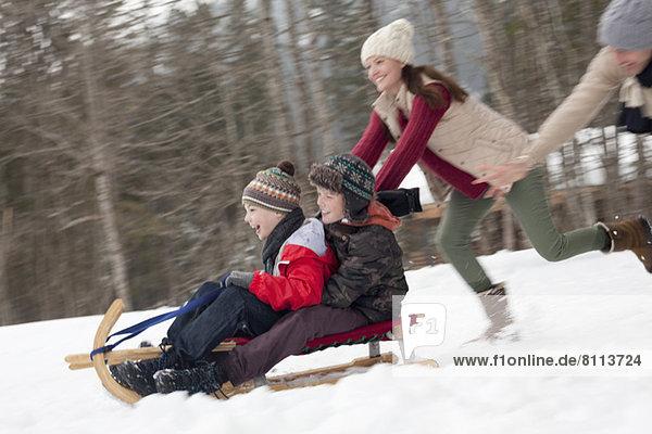 Enthusiastisches Familienrodeln im verschneiten Gelände