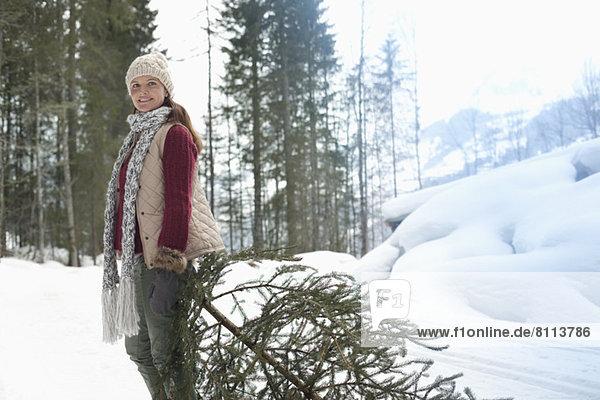 Porträt einer lächelnden Frau  die einen frischen Weihnachtsbaum im Schnee schleppt.