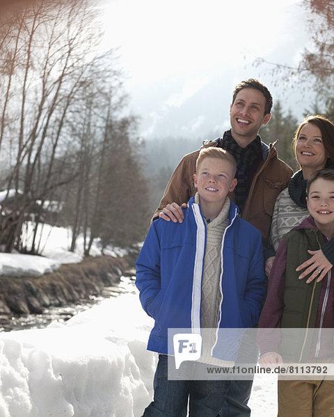 Glückliche Familie im Schnee stehend