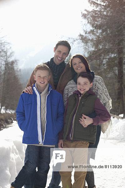 Porträt der lächelnden Familie in der verschneiten Gasse