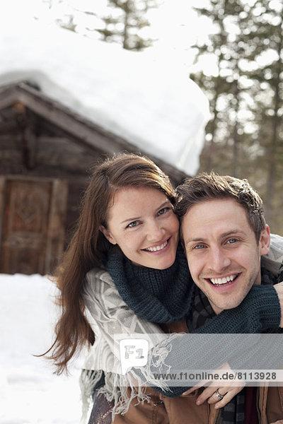 Portrait eines glücklichen Paares  das sich im Schnee außerhalb der Kabine umarmt.