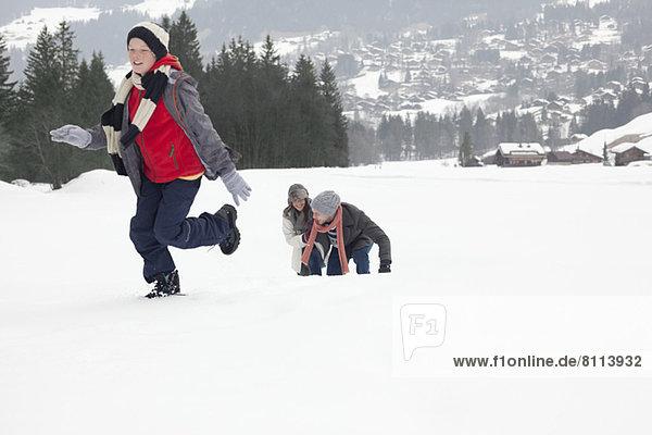 Mutter und Söhne spielen im Schneefeld