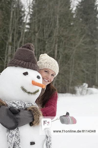 Glückliche Frau umarmt Schneemann im Wald