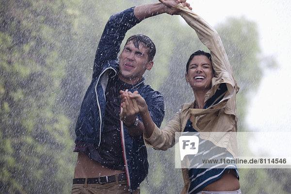 Glückliches Paar tanzt im Regen