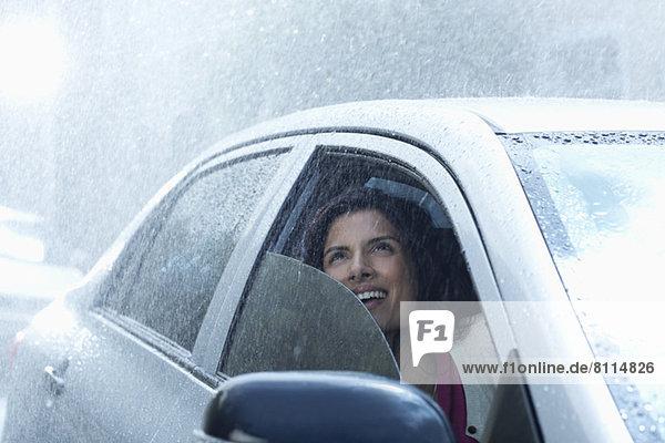 Lächelnde Geschäftsfrau im Auto mit Blick auf den Regen