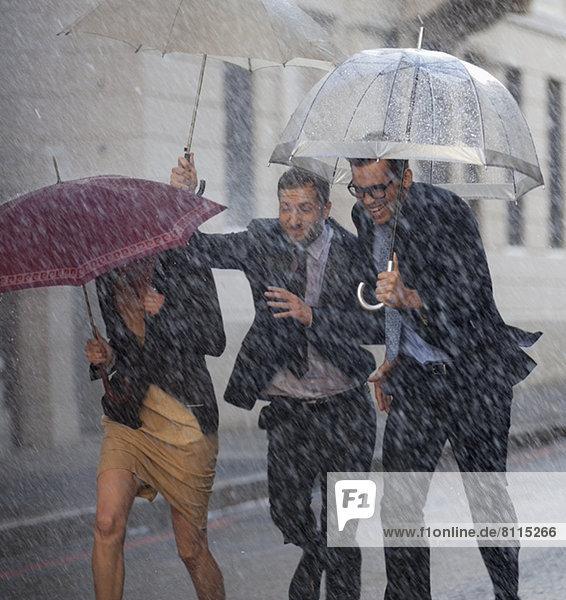 Fröhliche Geschäftsleute mit Regenschirmen in der verregneten Straße