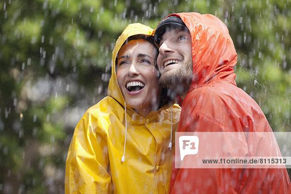 Glückliches Paar in Regenmänteln schaut auf den Regen.
