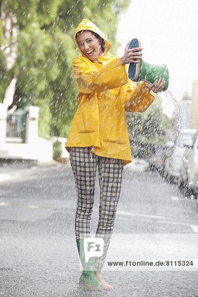 Porträt einer begeisterten Frau beim Entleeren des Stiefels bei Regen Porträt einer begeisterten Frau beim Entleeren des Stiefels bei Regen