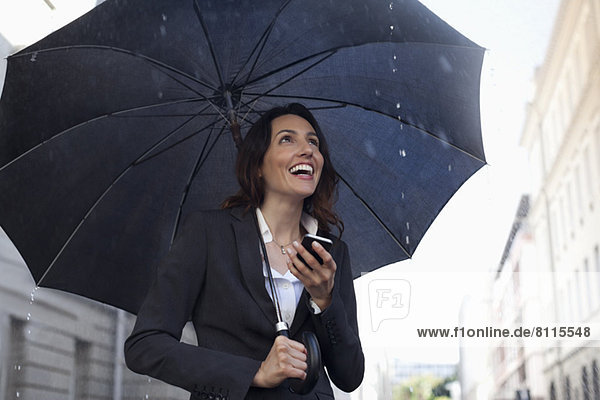 Glückliche Geschäftsfrau SMS mit Handy unter Schirm im Regen