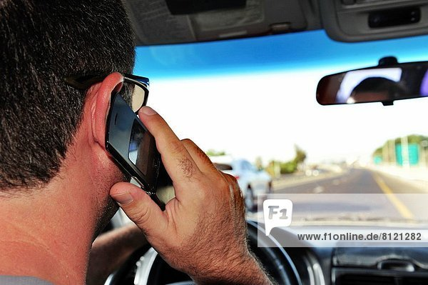 Concept photo of a male driver speaks on a mobile phone while driving.