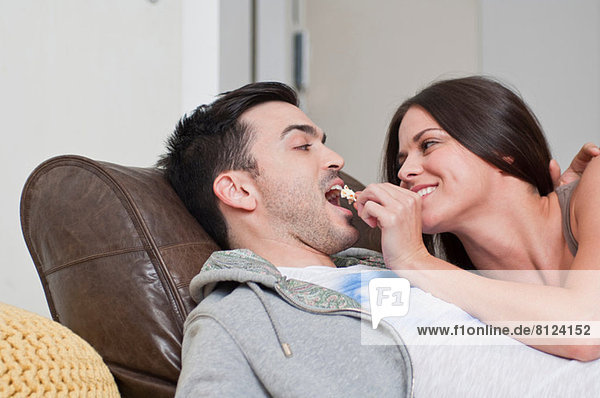Young couple lying on sofa sharing popcorn