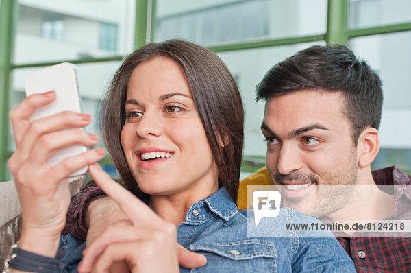 Junges Paar zu Hause  das sich das Handy teilt