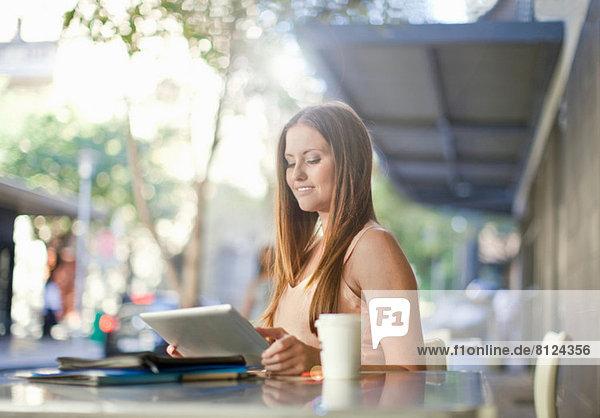 Junge Frau betrachtet digitales Tablett im Straßencafé