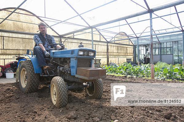 Bio-Bauer auf Traktor  der den Boden im Polytunnel pflegt
