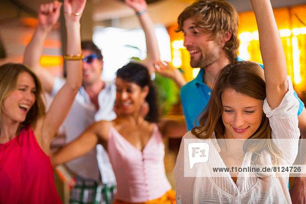 Freunde tanzen mit erhobenen Armen in der Bar.