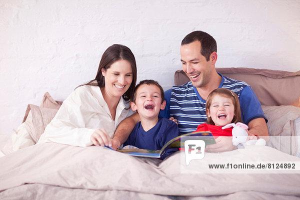 Eltern und zwei kleine Kinder schauen sich das Bilderbuch im Bett an.