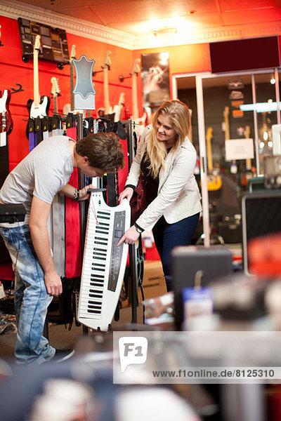 Junges Paar sucht Keytar im Musikladen
